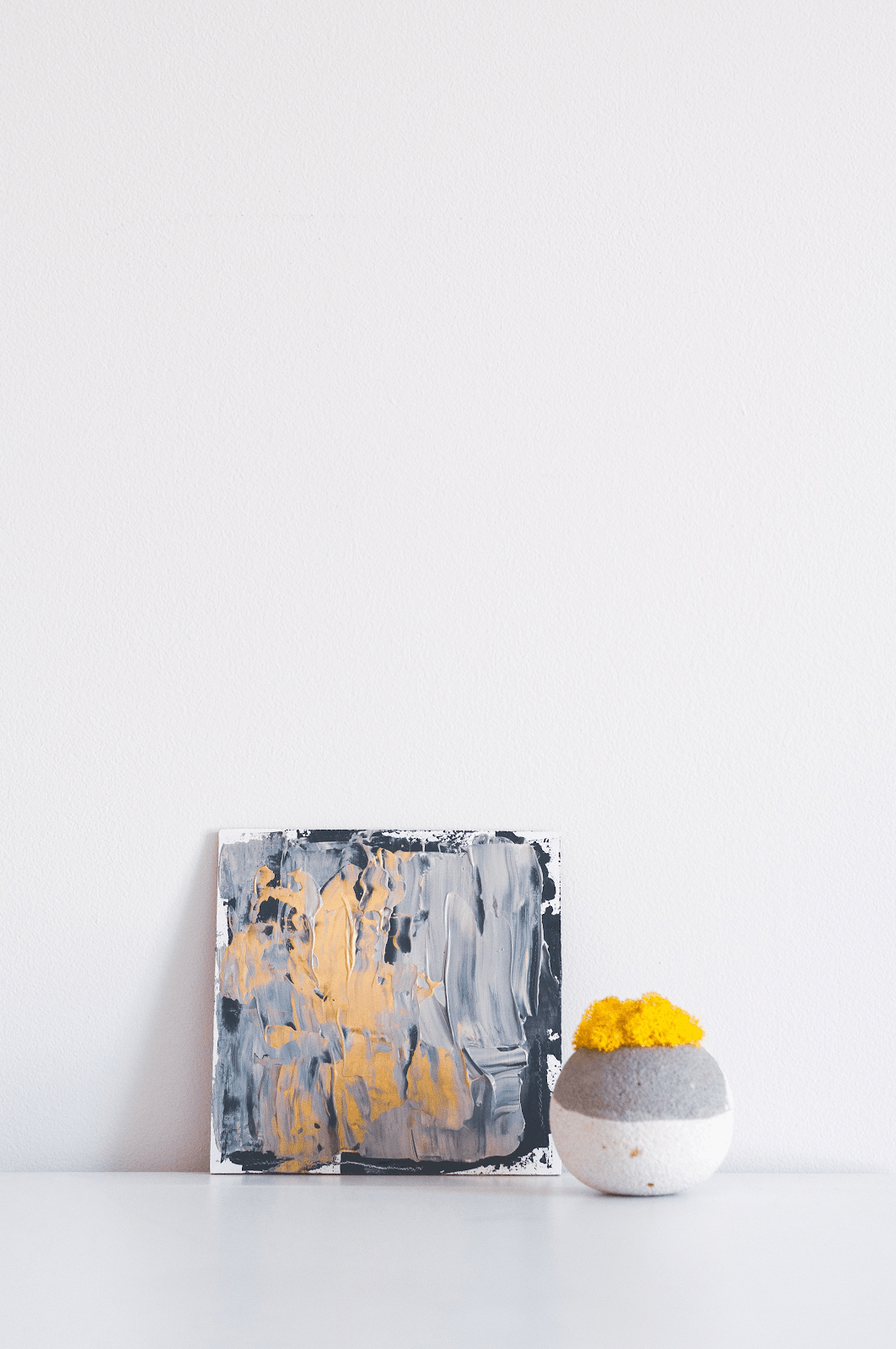 white wall with a painting on the floor