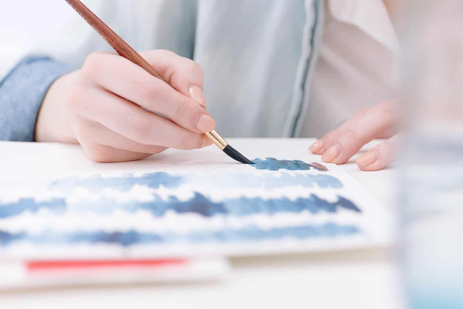 woman is painting with watercolor on paper