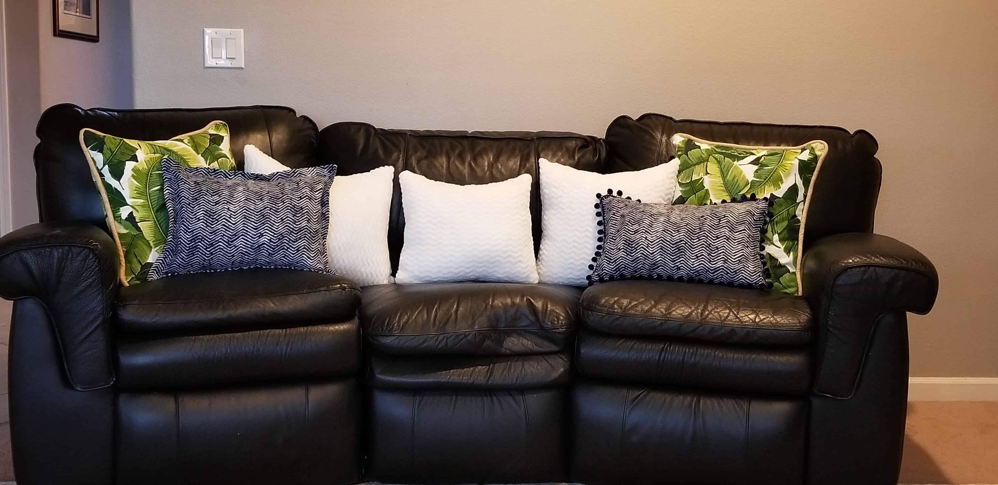 seven pillows on a black couch