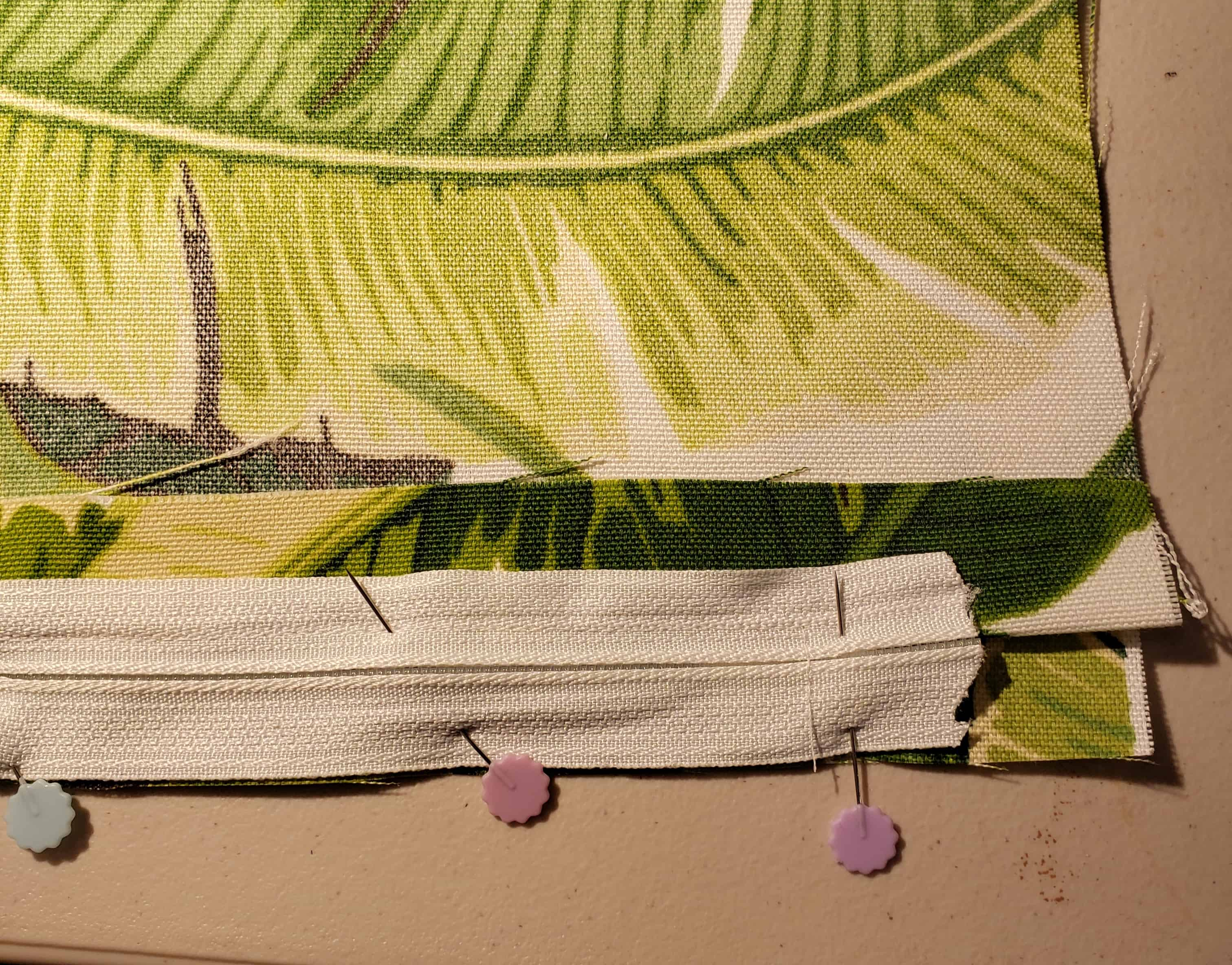 lining up the zipper tape side with a raw edge of fabric