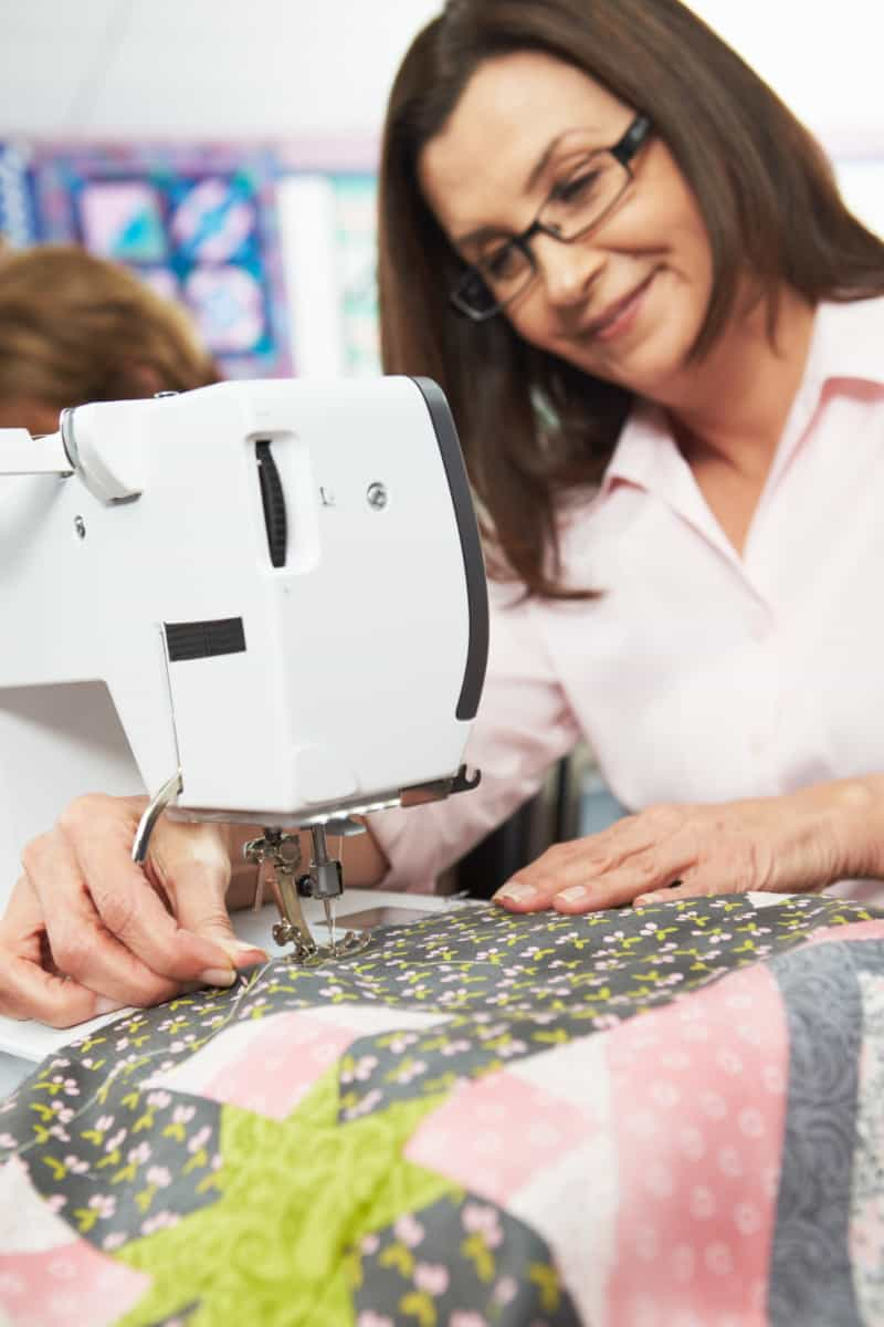 smiling woman sewing quilt Best Sewing Machines For Quilting verycreate.com