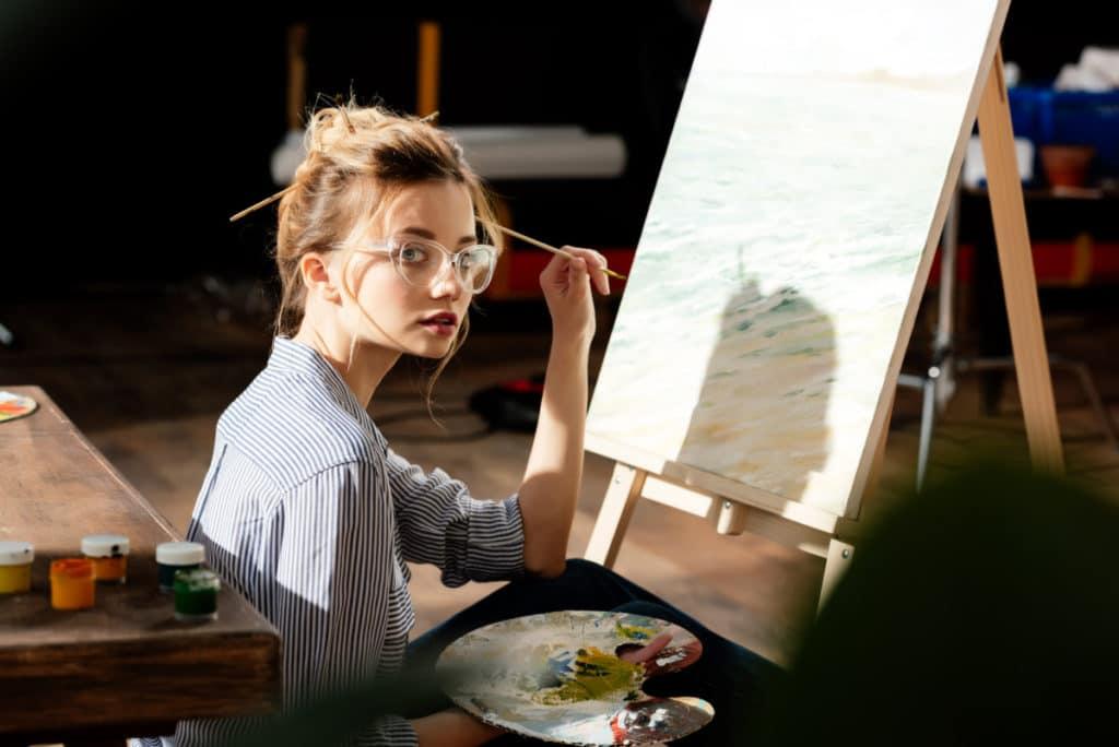 woman painting cast shadow best overhead lighting for art studio verycreate.com